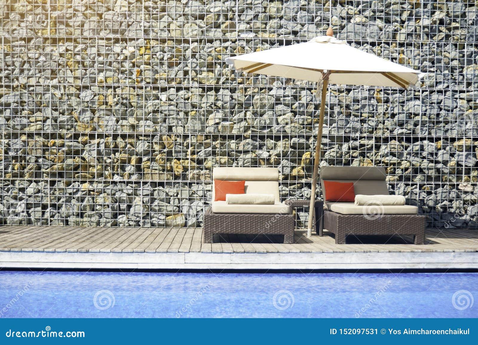 Atmósfera de relajación de los hoteles de la piscina con las paredes de piedra adornadas en el verano Silla a relajarse por la cu