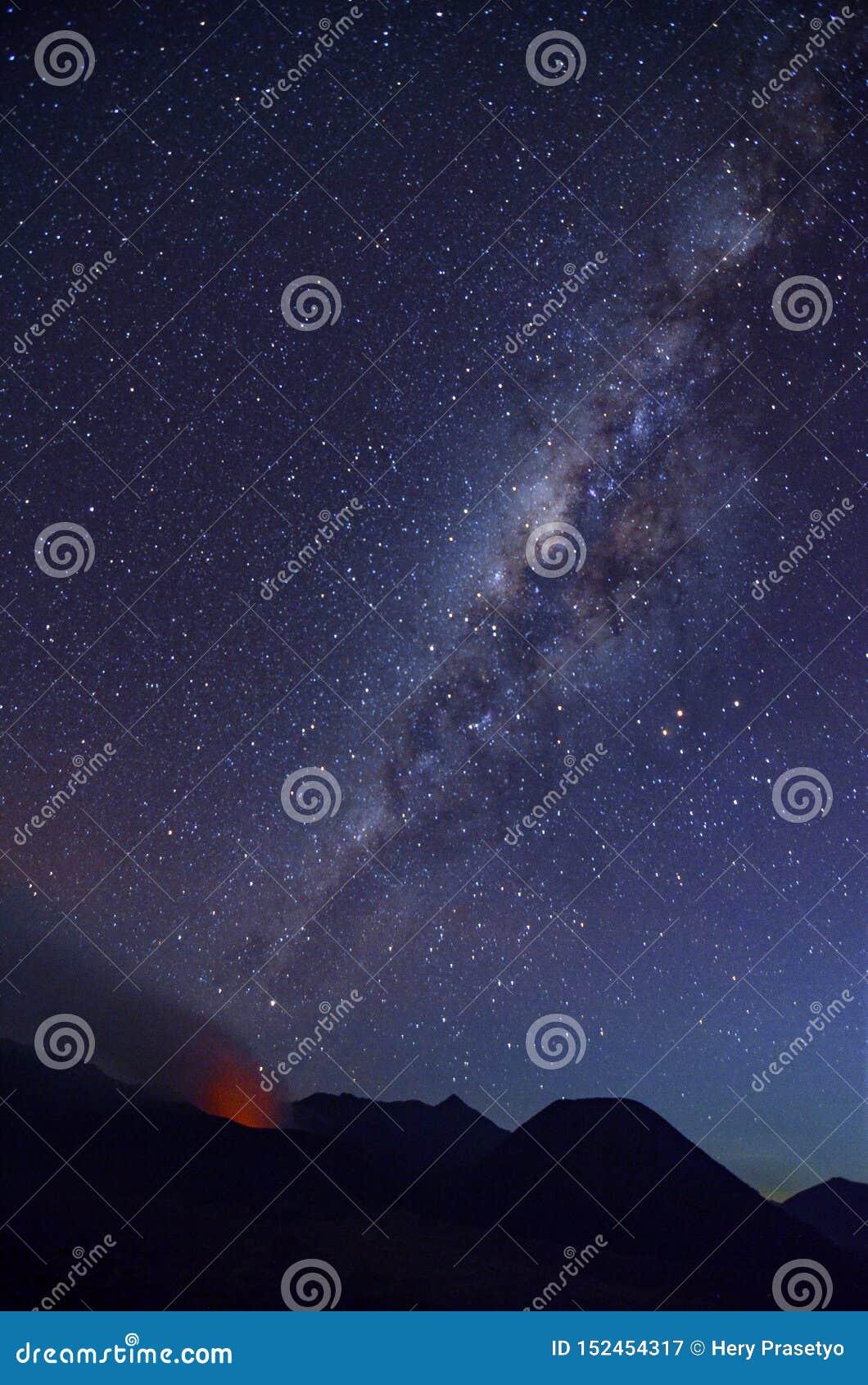 A atmosfera no deserto da montagem Bromo com nightscape e erupção