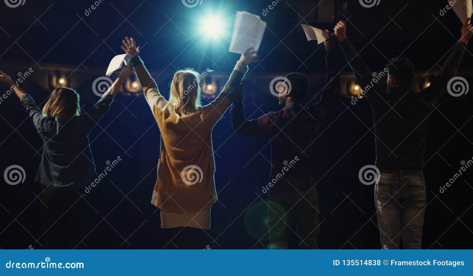 Atores que curvam-se à audiência em um teatro