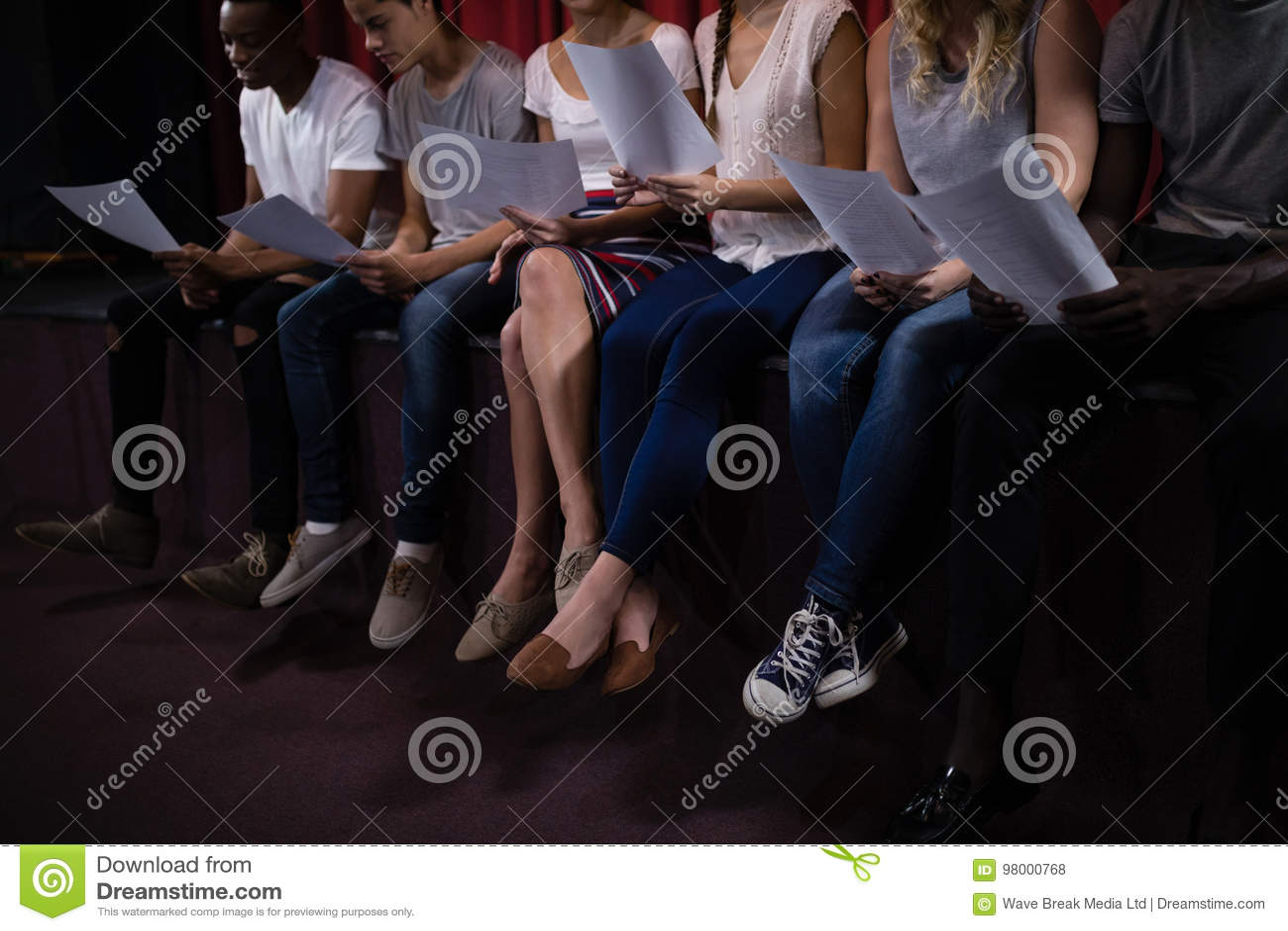 Atores que leem seus roteiros na fase no teatro