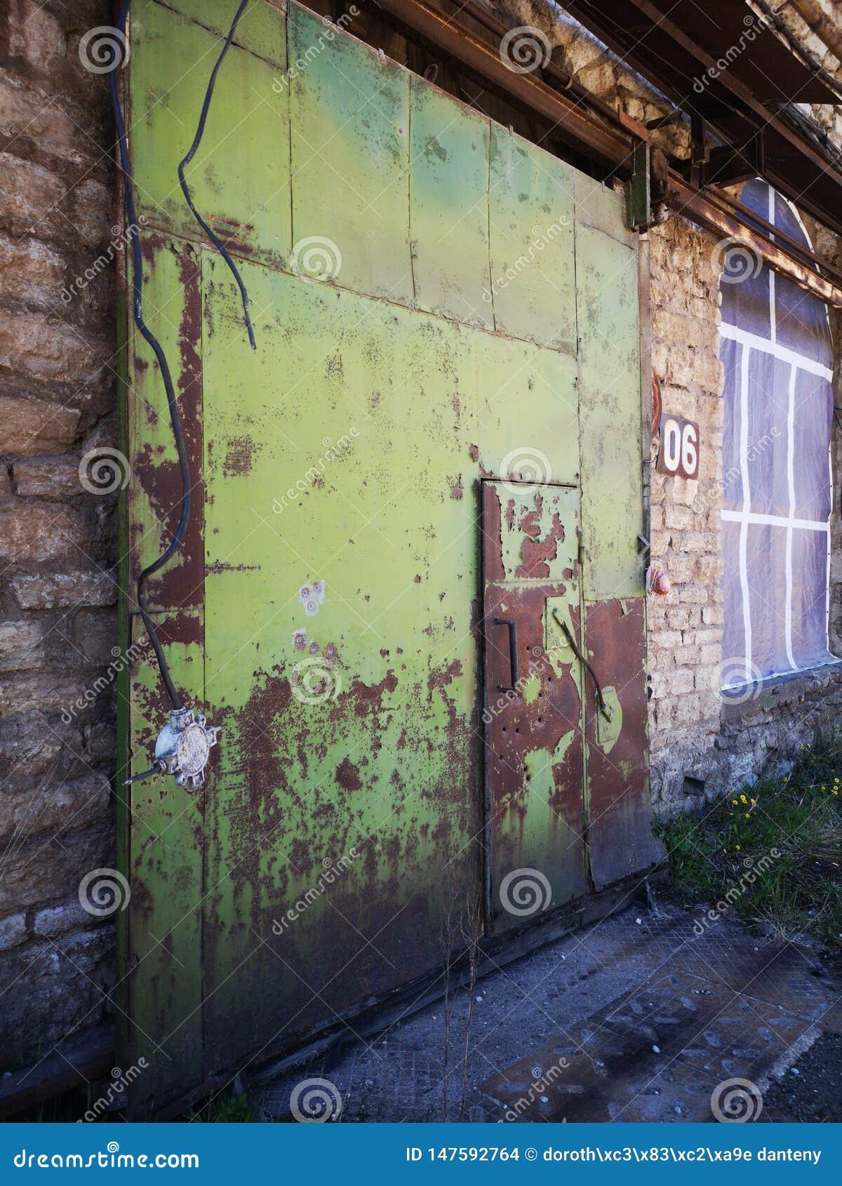 Atrás da fábrica abandonada contemporânea da arte da rua das portas