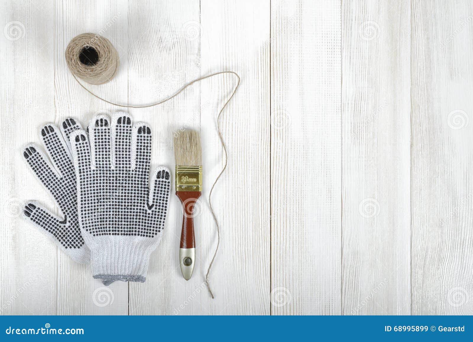 Atracción de la composición del arte de los guantes, del cepillo y de la guita mintiendo en la superficie de madera blanca