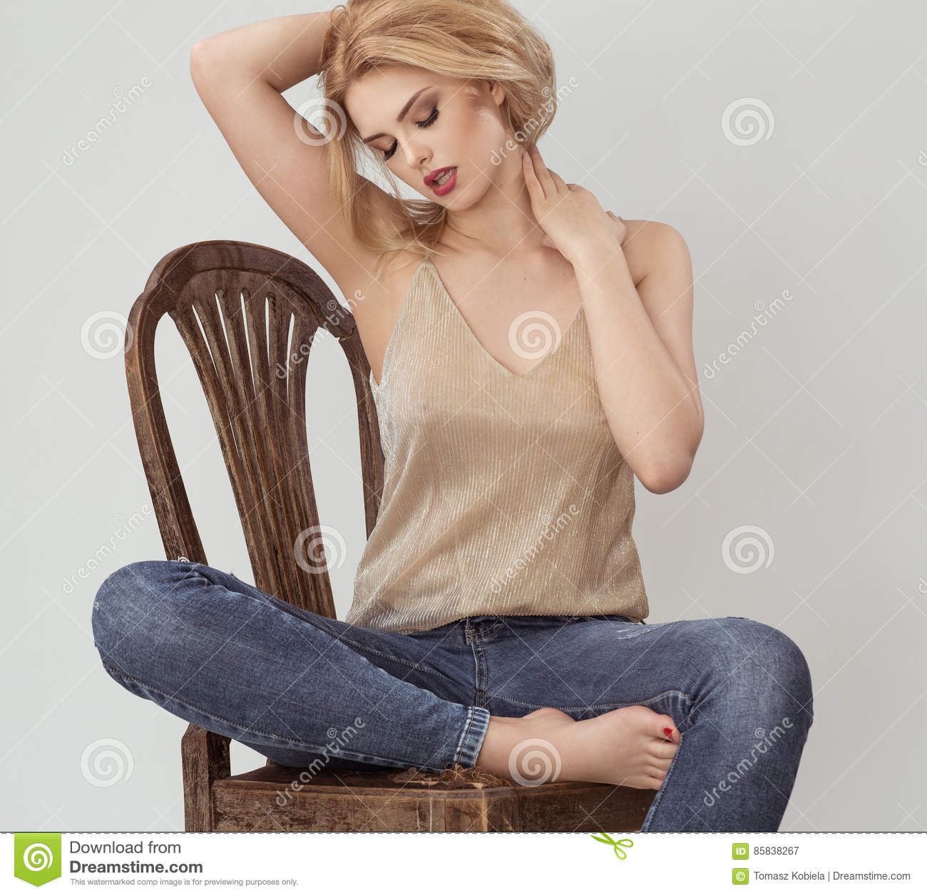 Atractive woman in gold shirt sitting on the brown chair