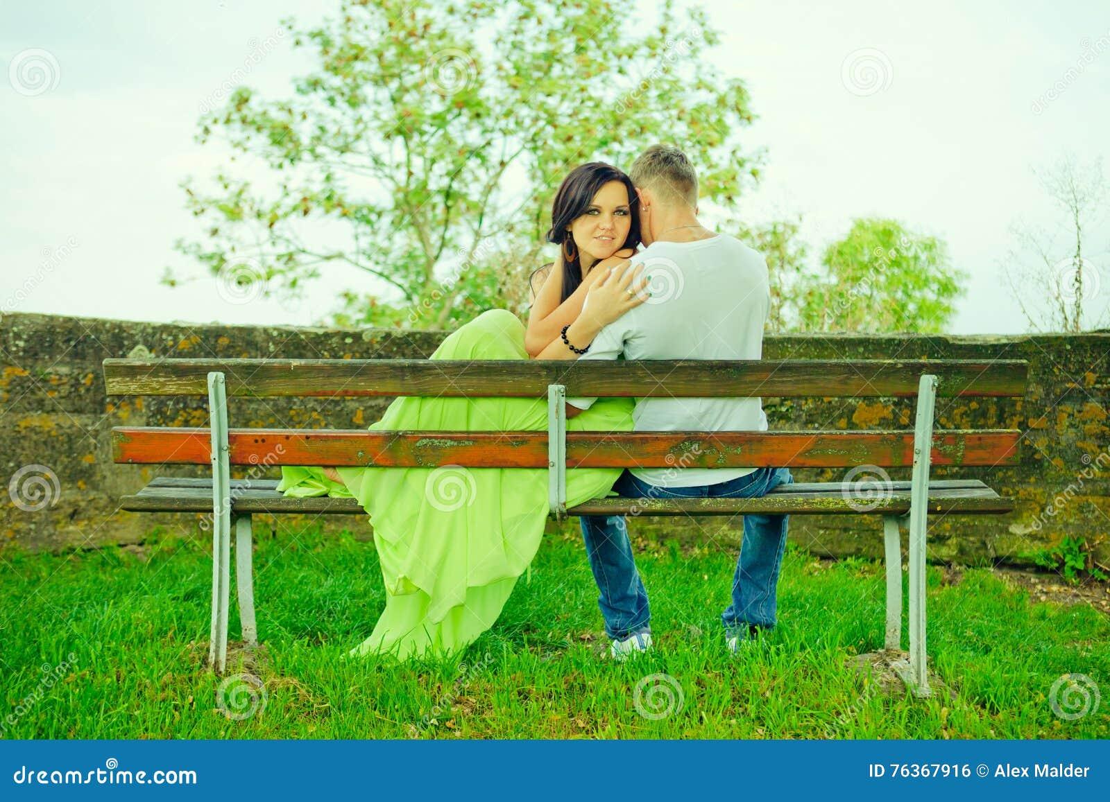 Atractivo el individuo con la muchacha se sienta y abraza en un banco