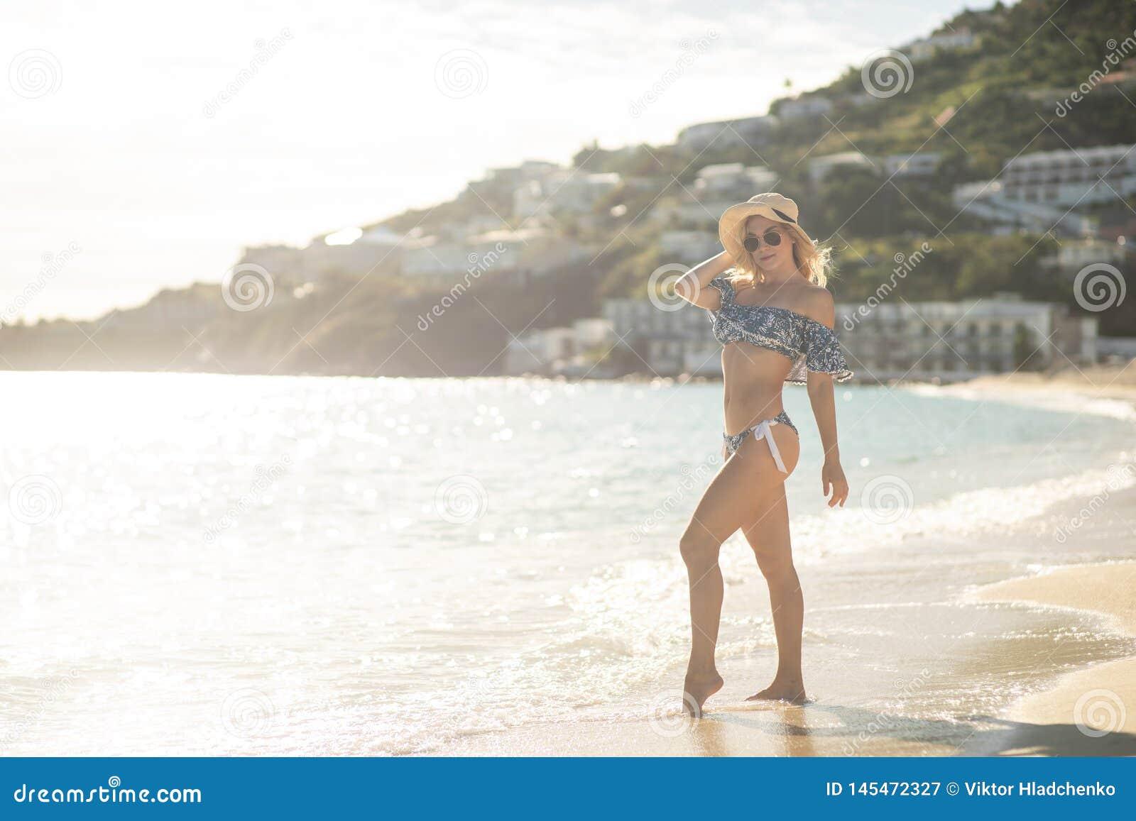 Atrakcyjna blondynki m?oda kobieta jest ubranym swimsuit przy tropikaln? piasek pla?? z mi?kkim ?wiat?em s?onecznym