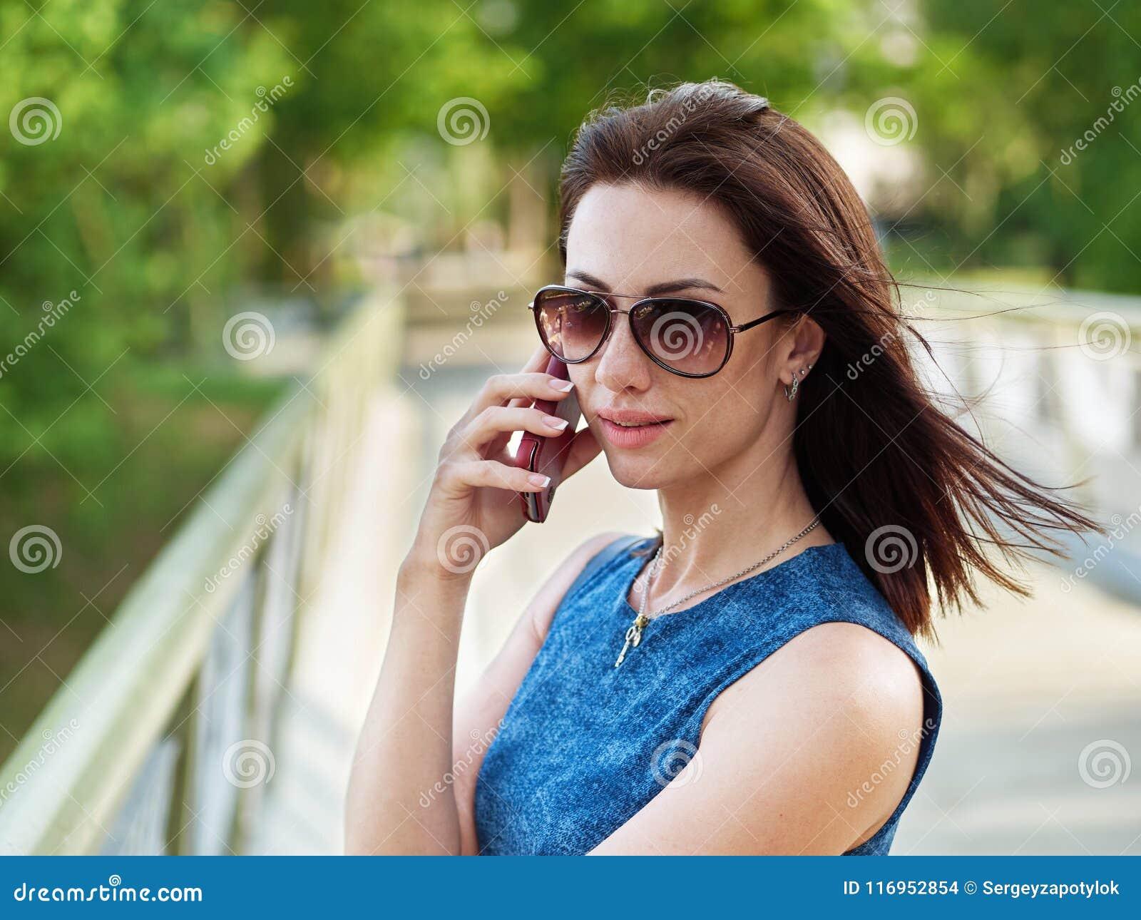 Atrakcyjna brunetki kobieta w okularach przeciwsłonecznych i niebiescy dżinsy sukni emocjonalną rozmowę telefoniczną na telefonie