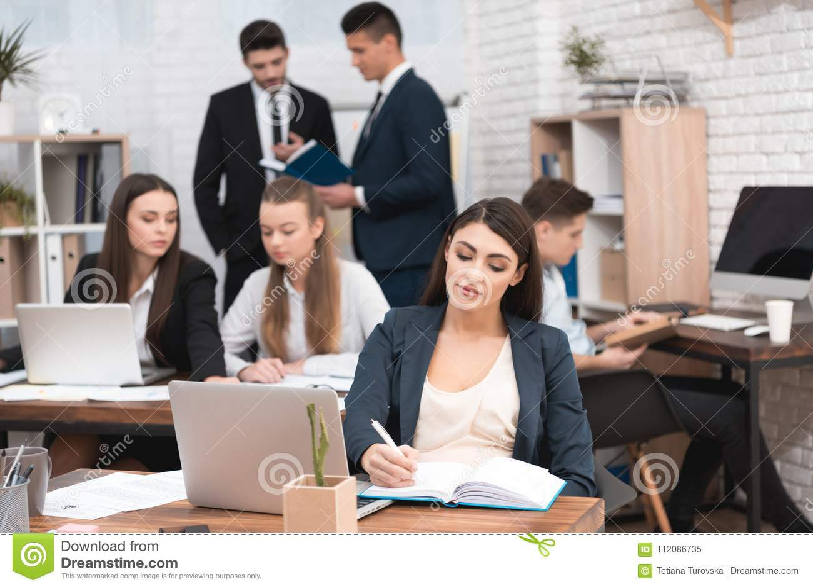 Atrakcyjna ciężarna dziewczyna pracuje w biurze z kolegami Ciężarny bizneswoman w workspace maternity