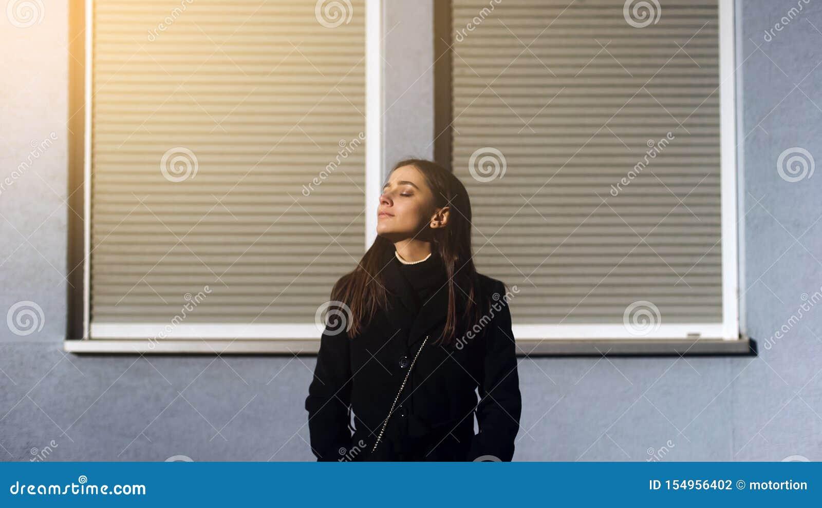 Atrakcyjna inspirowana młoda dama stoi outdoors na świetle słonecznym, cieszy się dobrego dzień