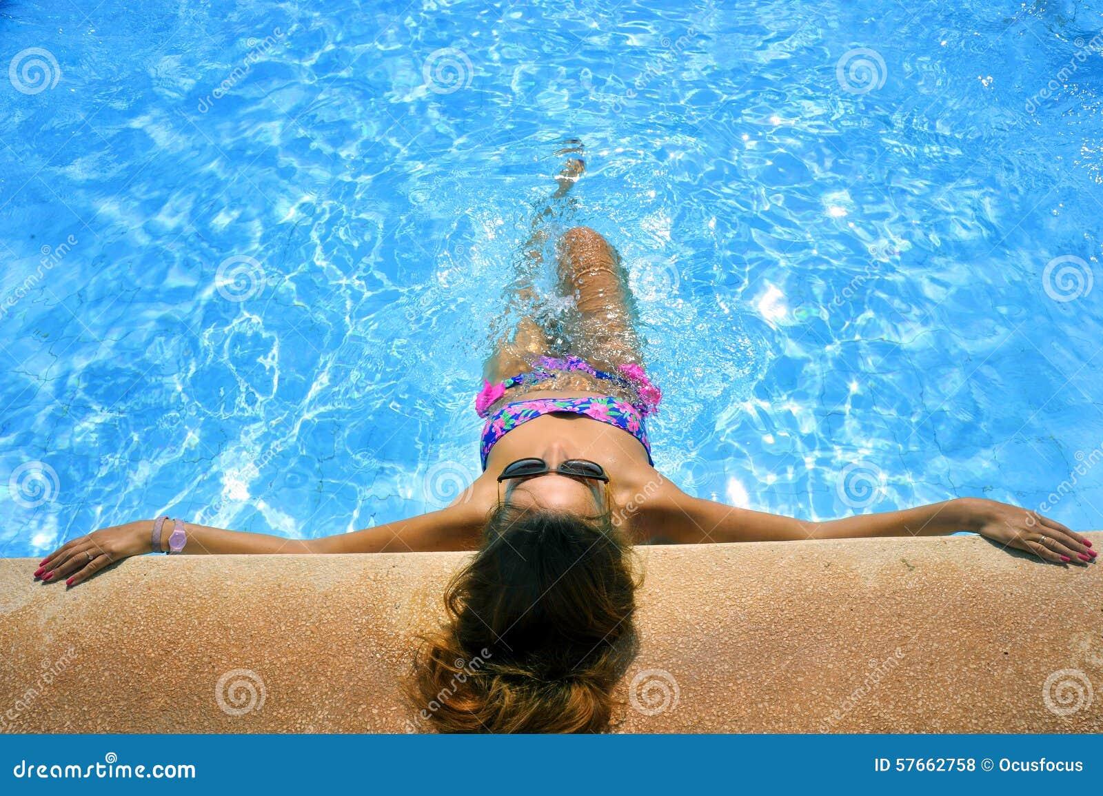 Atrakcyjna kobieta w bikini i okularów przeciwsłonecznych sunbathing opierać na krawędzi wakacje kurortu pływacki basen