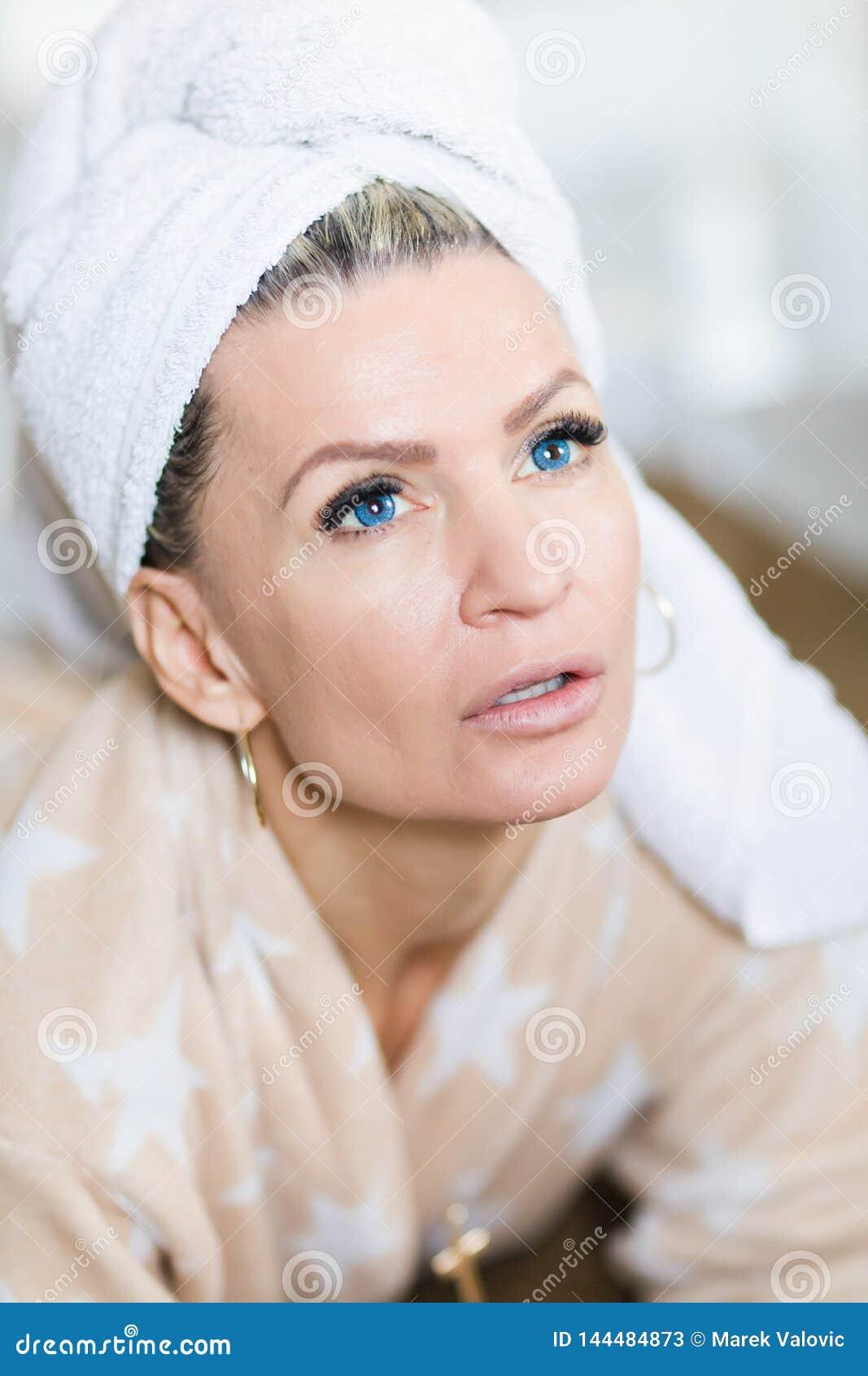 Atrakcyjna kobieta z błękitnymi szkłami kontaktowymi z ręcznikiem na głowie po relaksu