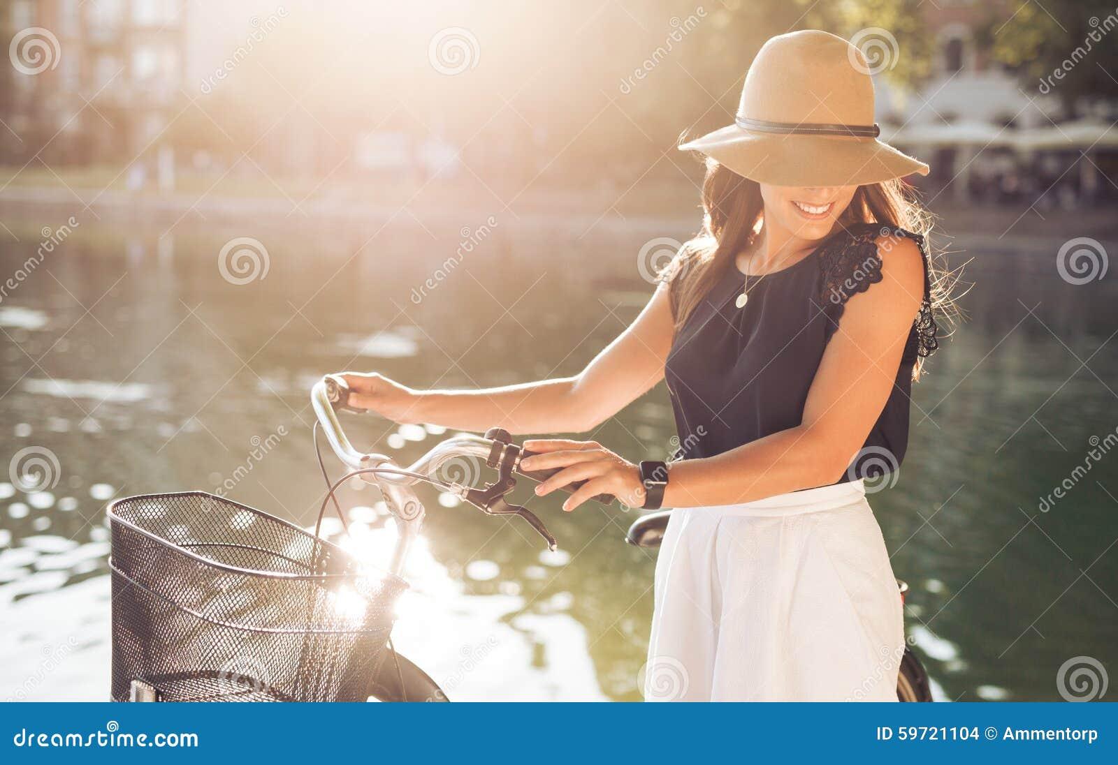 Atrakcyjna kobieta z rowerem przy parkiem