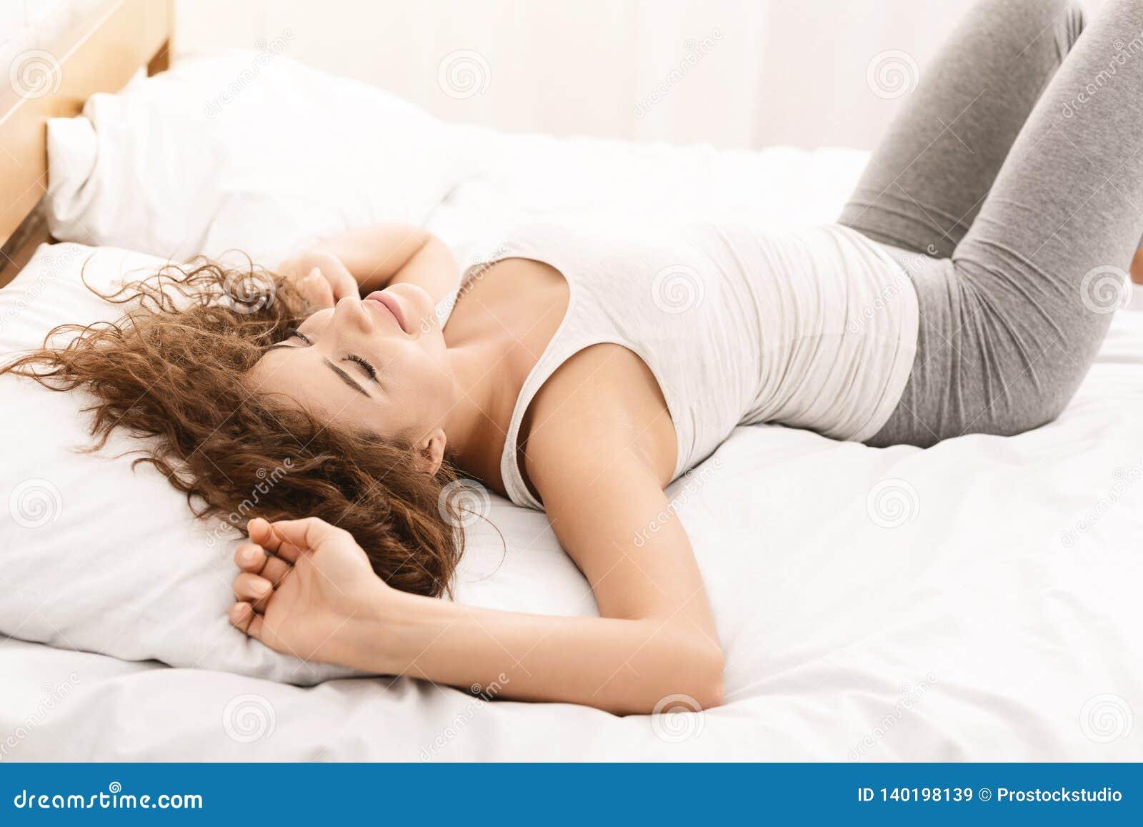 Atrakcyjna młoda kobieta ono uśmiecha się w łóżku w domu