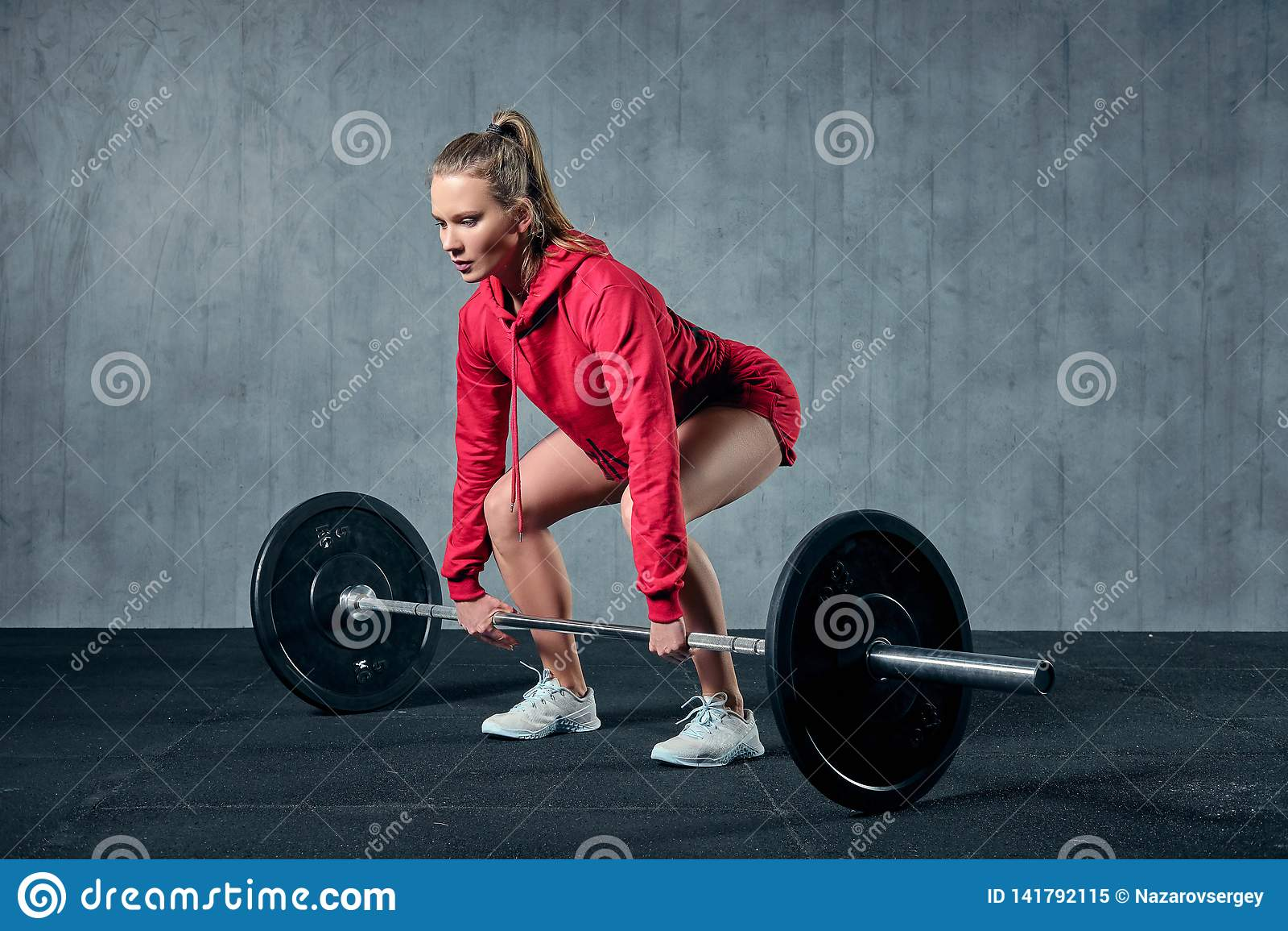 Atrakcyjna młoda sporty kobieta jest pracująca w gym out Mięśniowa kobieta kuca z barbell