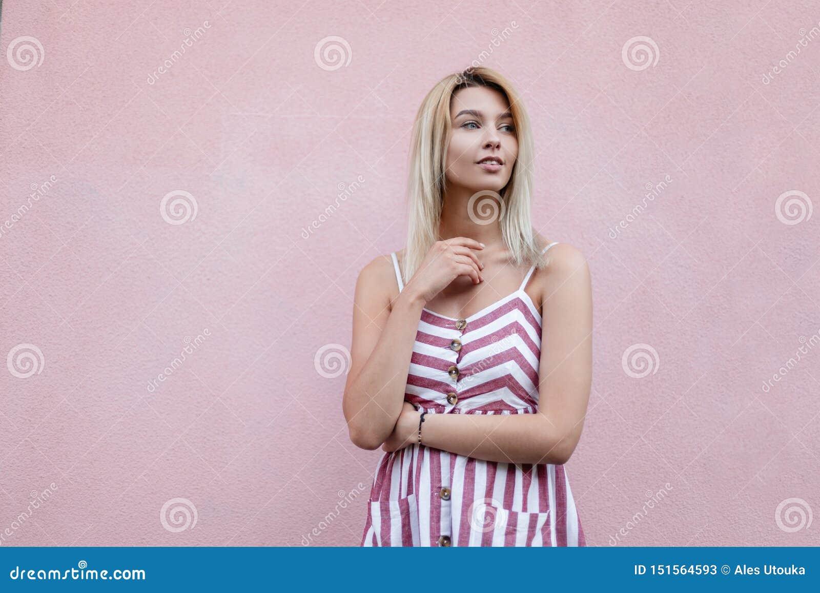 Atrakcyjna młoda blondynki kobieta w lata eleganckich pasiastych sundress odpoczywa blisko różowej rocznik ściany w mieście Pi?kn