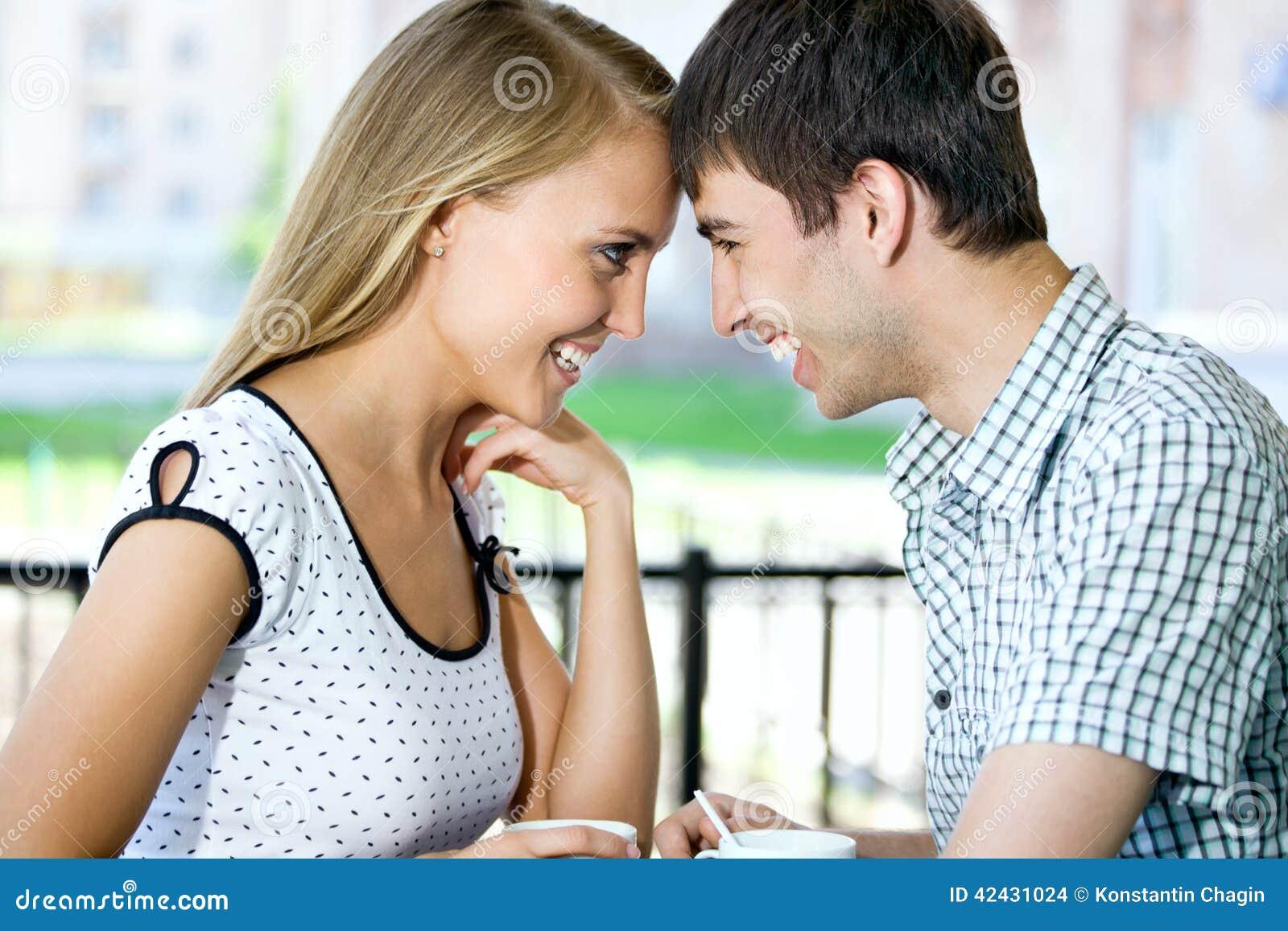 Atrakcyjna młoda kobieta pije kawę z jej chłopakiem