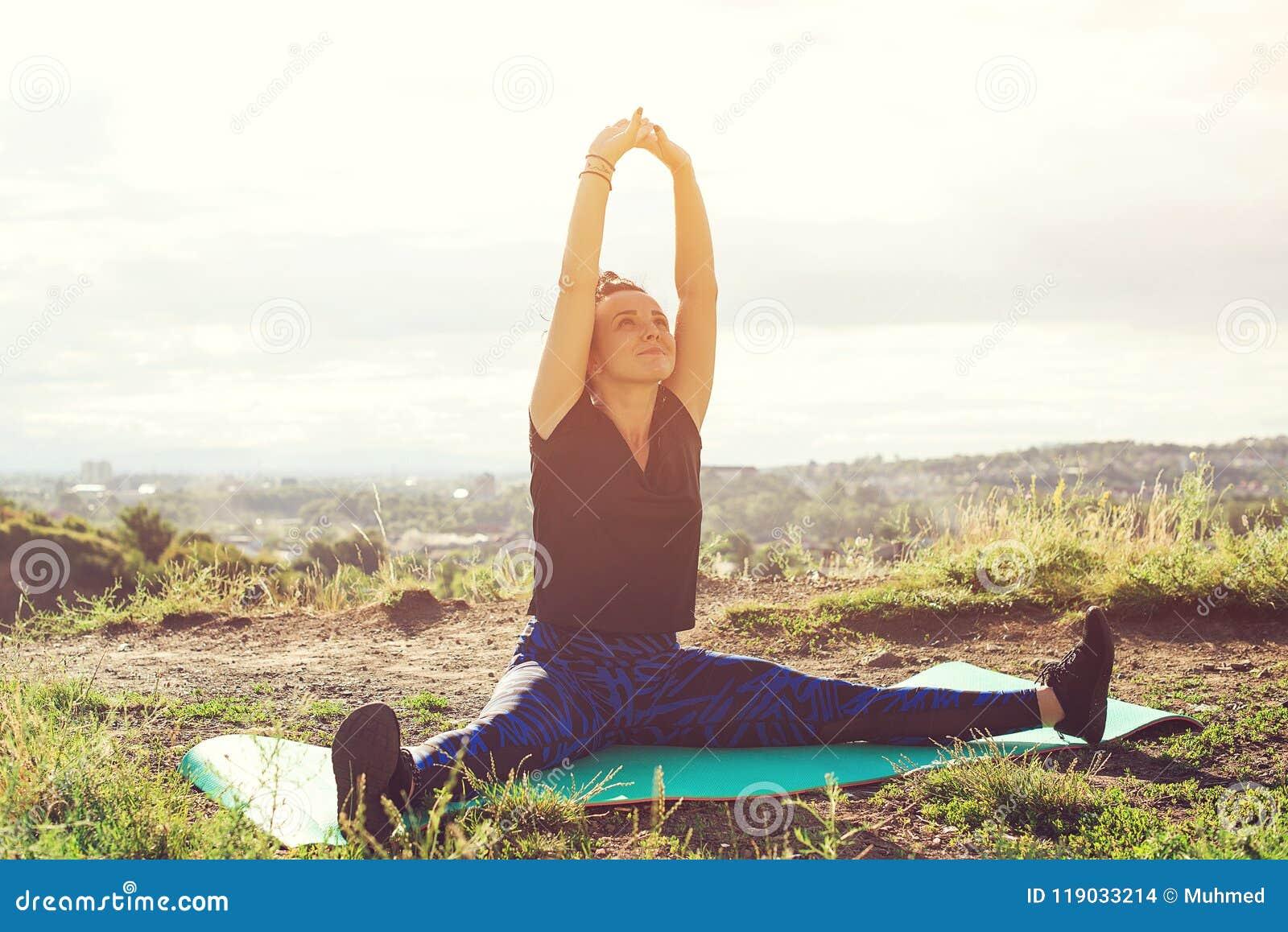Atrakcyjna młoda kobieta robi ćwiczeniom na wzgórzu nad miastem przy zmierzchem