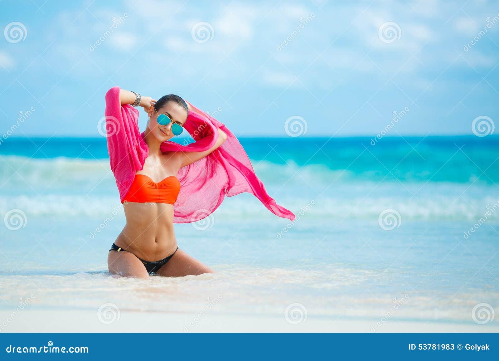 Atrakcyjna młoda kobieta z czerwonym pareo na plaży