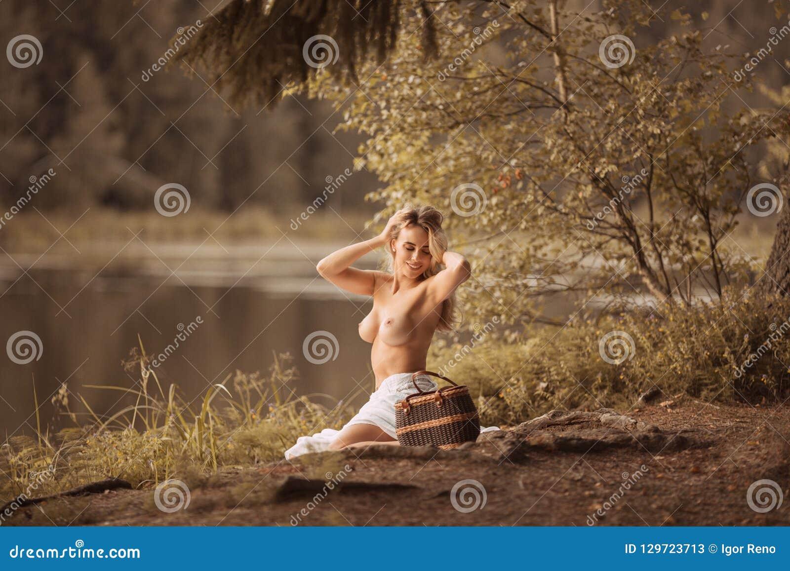 Atrakcyjna młoda kobieta z pięknego długiego blondynu siedzącym toples