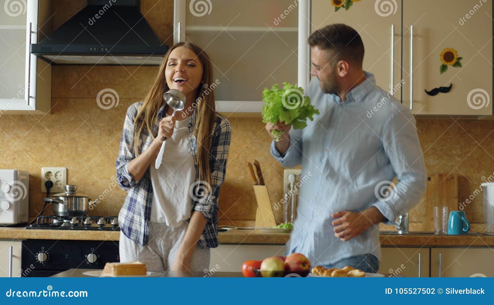 Atrakcyjna młoda radosna para zabawa śpiew i tana w kuchni podczas gdy gotujący w domu