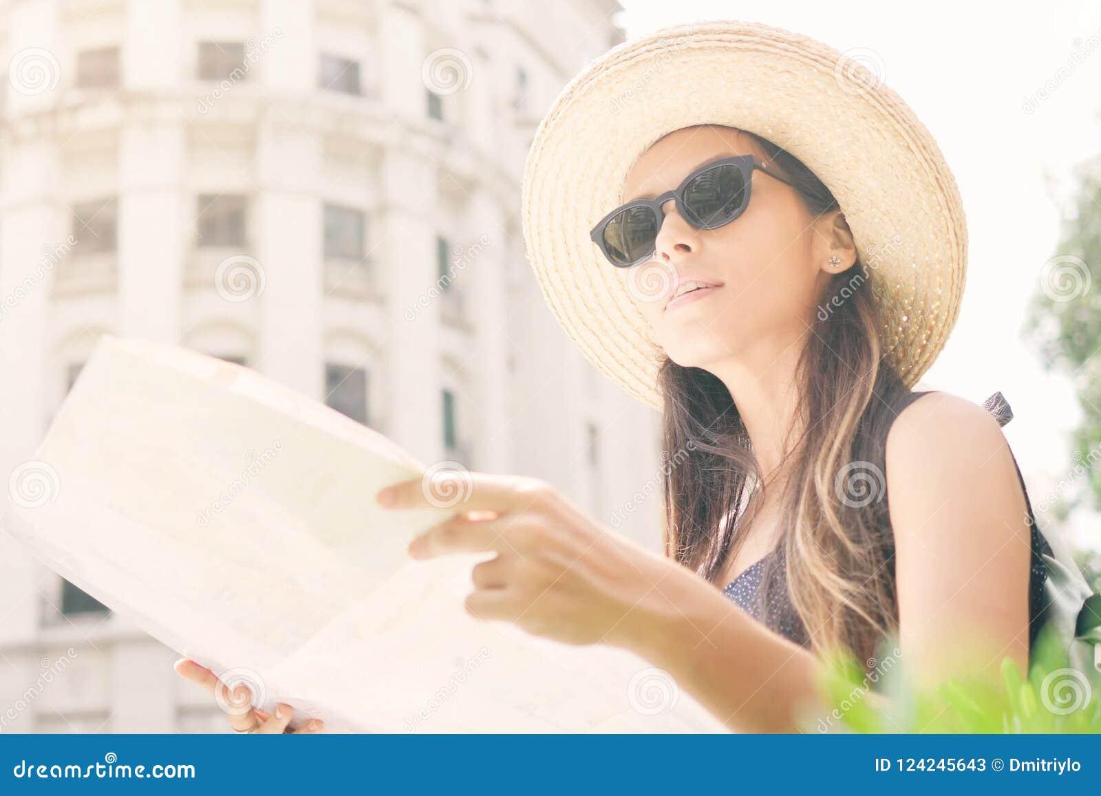 Atrakcyjna Młoda Turystyczna dziewczyny pozycja na Starej ulicie z miasto mapą Wokoło spojrzeniem i