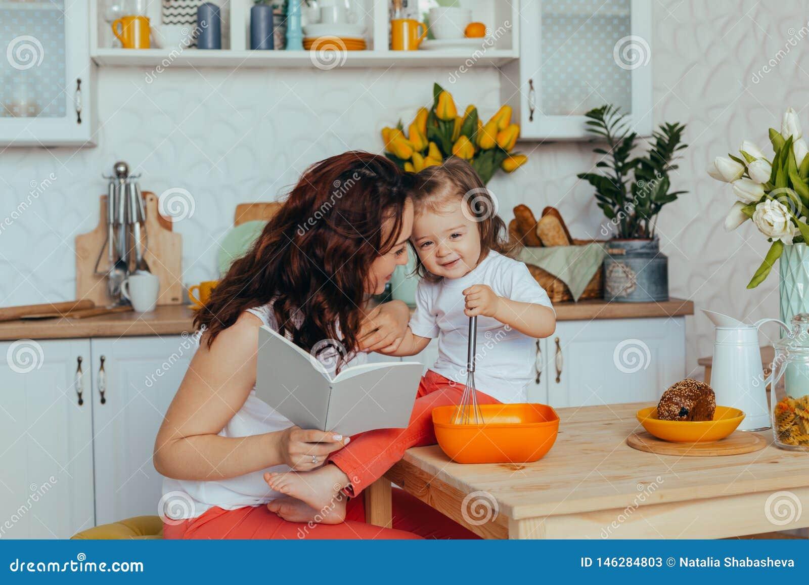 Atrakcyjna m?oda kobieta i jej ma?a ?liczna c?rka gotujemy na kuchni