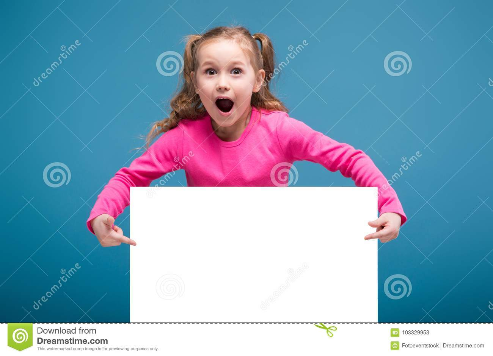 Atrakcyjna mała śliczna dziewczyna w różowej koszula z małpiego i błękitnego spodnie chwyta pustym plakatem
