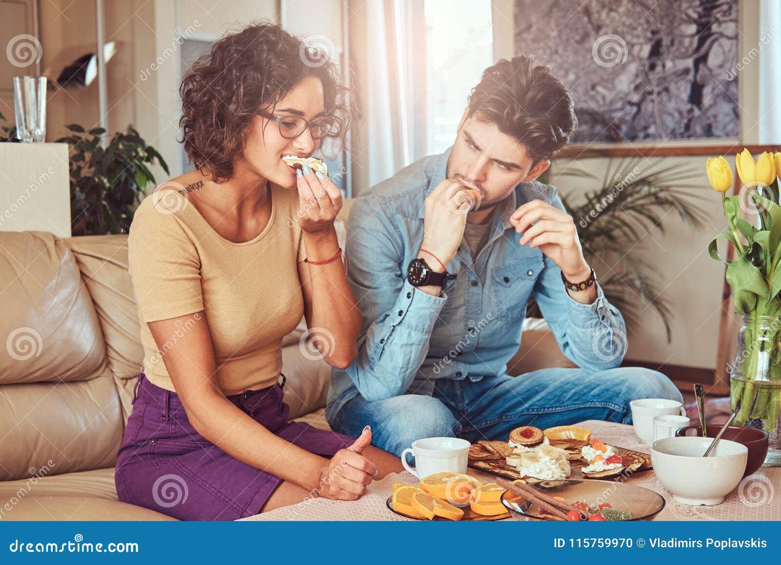 Atrakcyjna para, przystojny brodaty elegancki facet i kędzierzawa piękno dziewczyna je posiłek w domu,