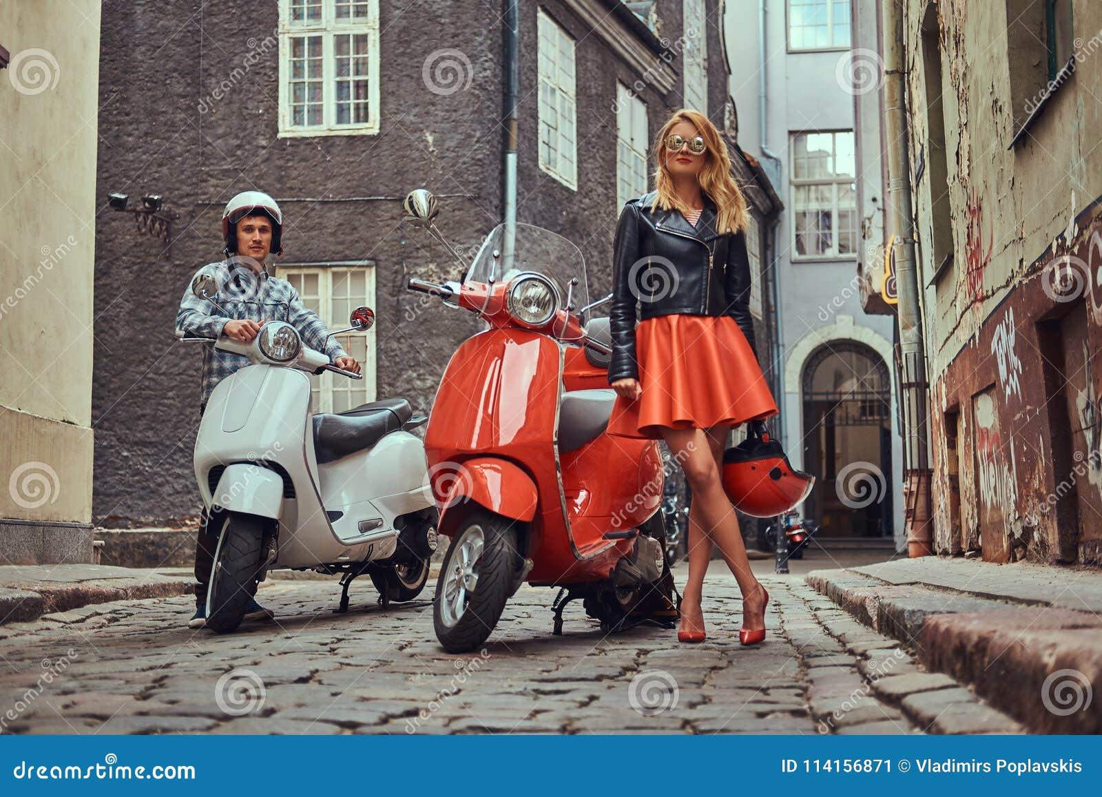 Atrakcyjna para, przystojny mężczyzna i seksowna żeńska pozycja na starej ulicie z dwa retro hulajnoga,