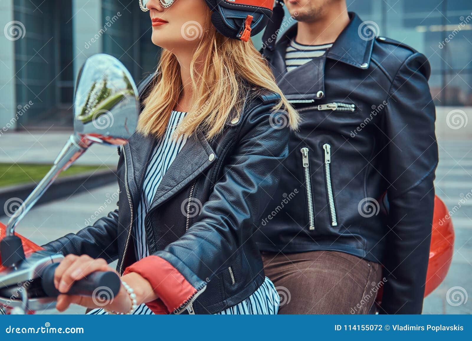 Atrakcyjna para, przystojny mężczyzna wpólnie i seksowna żeńska jazda na czerwonej retro hulajnoga w mieście,