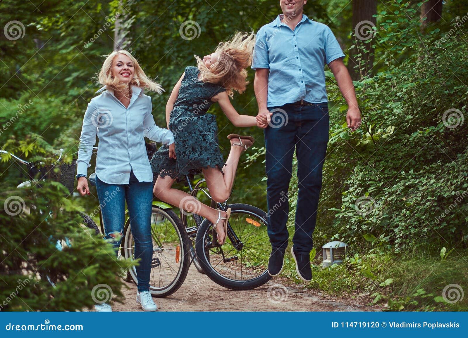 Atrakcyjna rodzina ubierał w przypadkowych ubraniach na rowerowej przejażdżce, w parku, zabawę i doskakiwanie