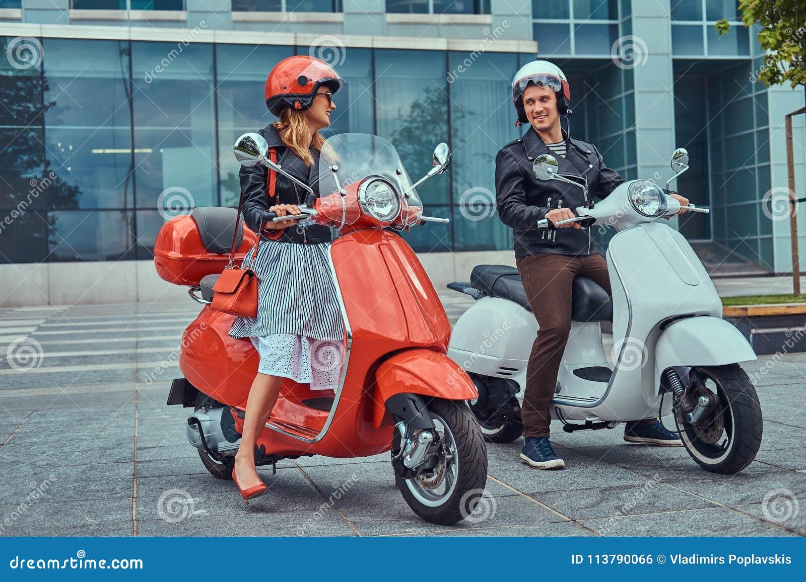 Atrakcyjna romantyczna para, przystojny mężczyzna i seksowna kobieta stoi z dwa retro Włoskimi hulajnoga przeciw a,