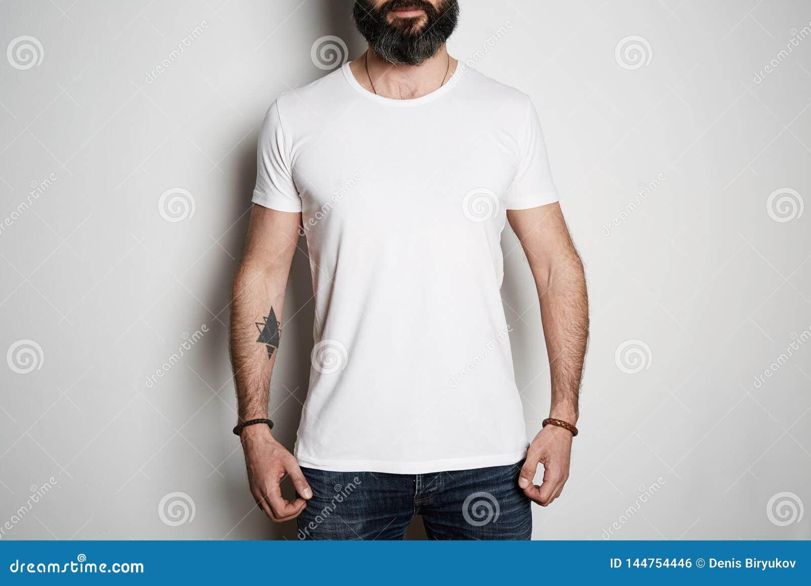 Atrakcyjne brutalne tatuować brodate facet pozy w niebieskich dżinsach i puste miejsce koszulki premii lata szarej bawełnie na