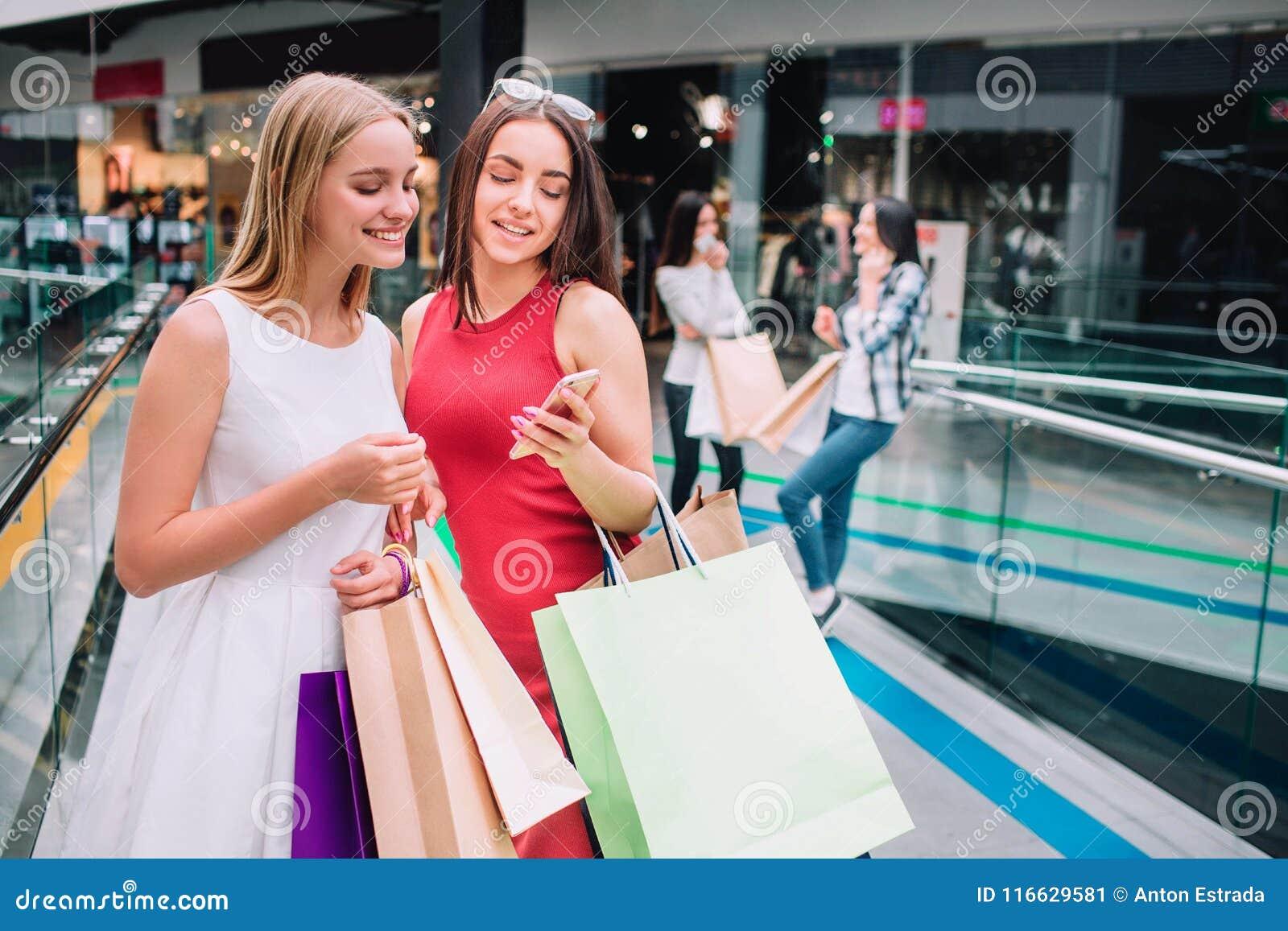 Atrakcyjne i piękne dziewczyny stoją wraz z torbami Brunetki dziewczyna trzyma telefon i patrzeje je
