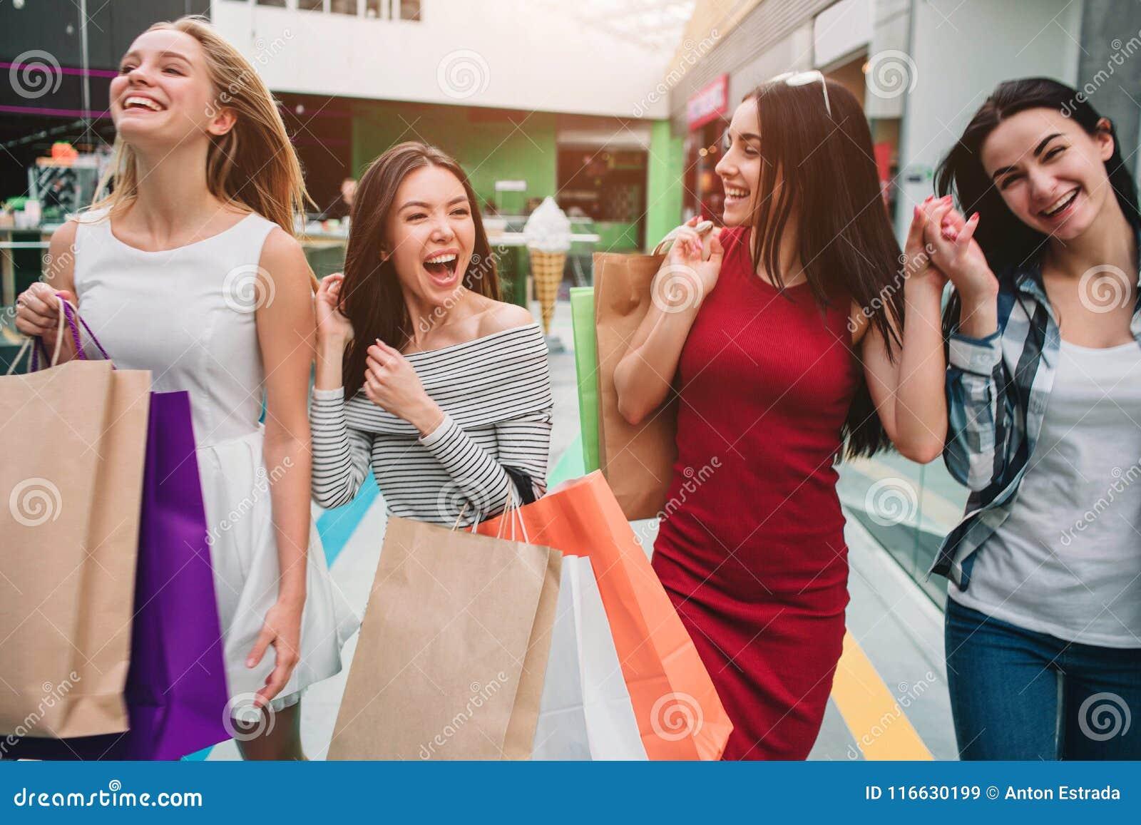 Atrakcyjne i zadowolone dziewczyny chodzą w centrum handlowym wpólnie Trzymają torby z materiałem Dziewczyny są roześmiane i