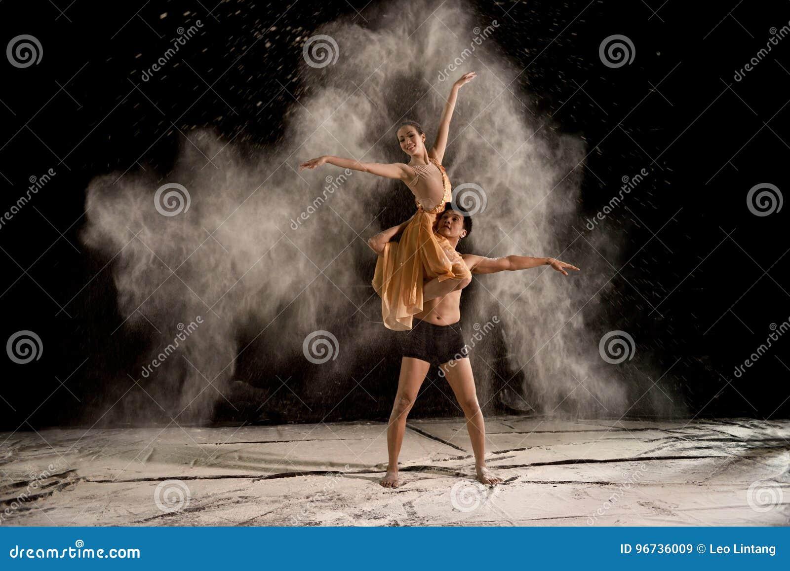 Atrakcyjnej pary baletniczy tancerz z bielu proszkiem w powietrzu