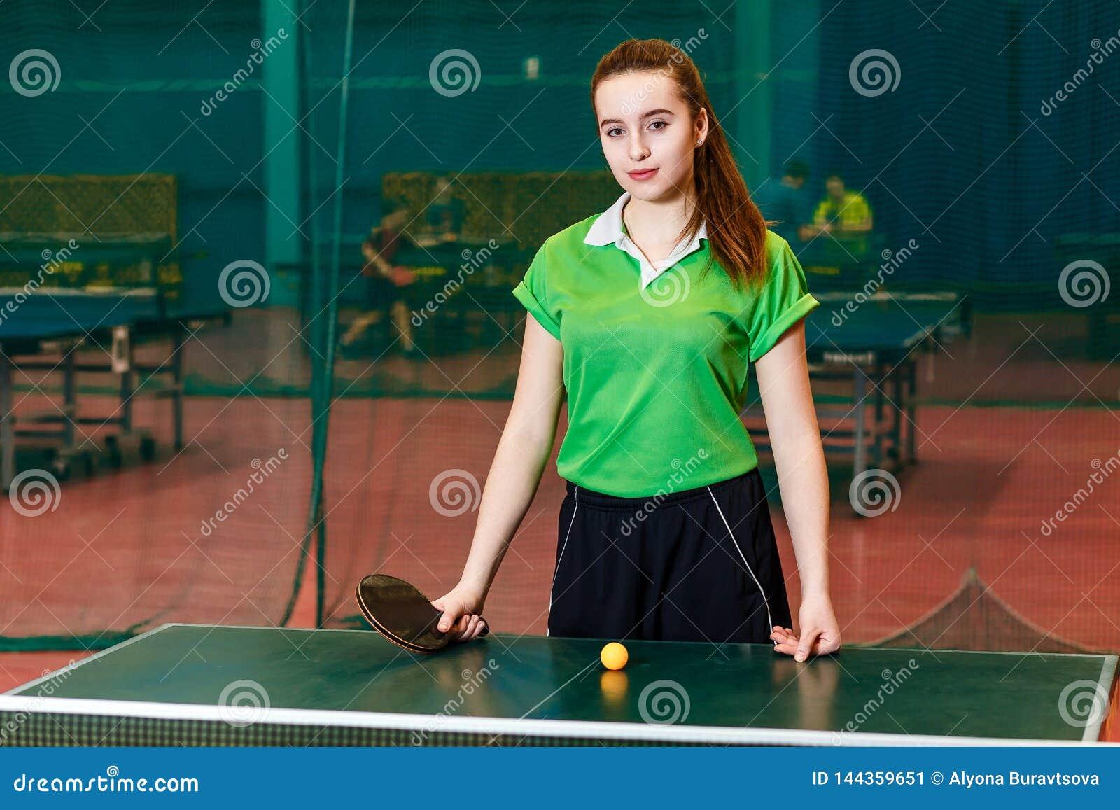 Atrakcyjni Kaukascy nastoletni dziewczyna stojaki blisko stołowego tenisa i spojrzenia przy kamerą M?oda sportsmenka