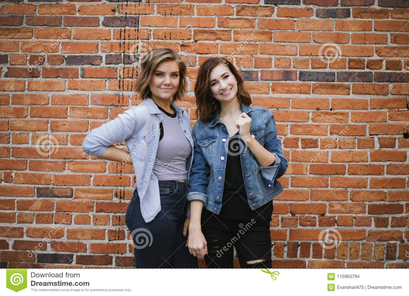 Atrakcyjni Młodzi Żeńscy najlepsi przyjaciele Modeluje zabawę przed Ceglaną Miastową ścianą i Ma