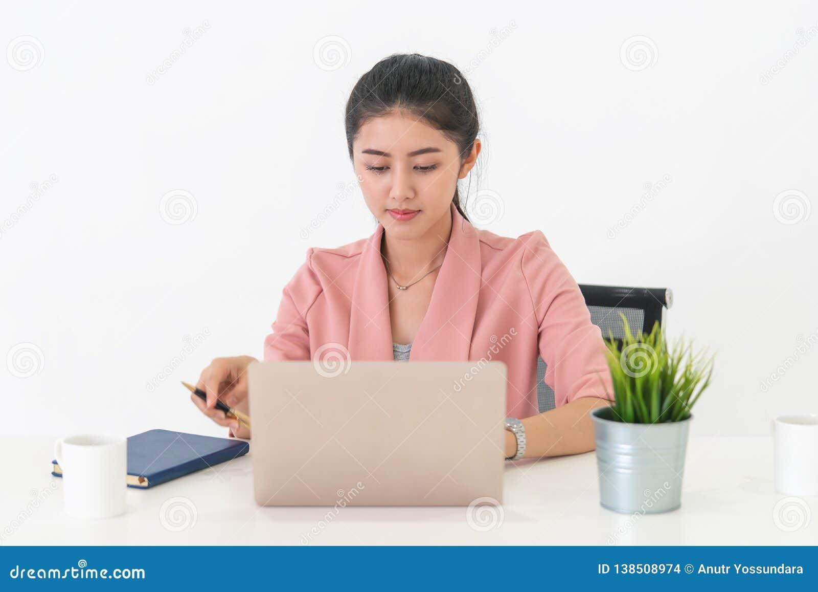 Atrakcyjny bizneswoman pracuje na laptopie w jej biurowym biurku