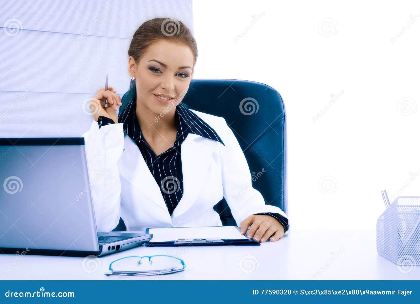 Atrakcyjny bizneswoman pracuje z laptopem przy biurem