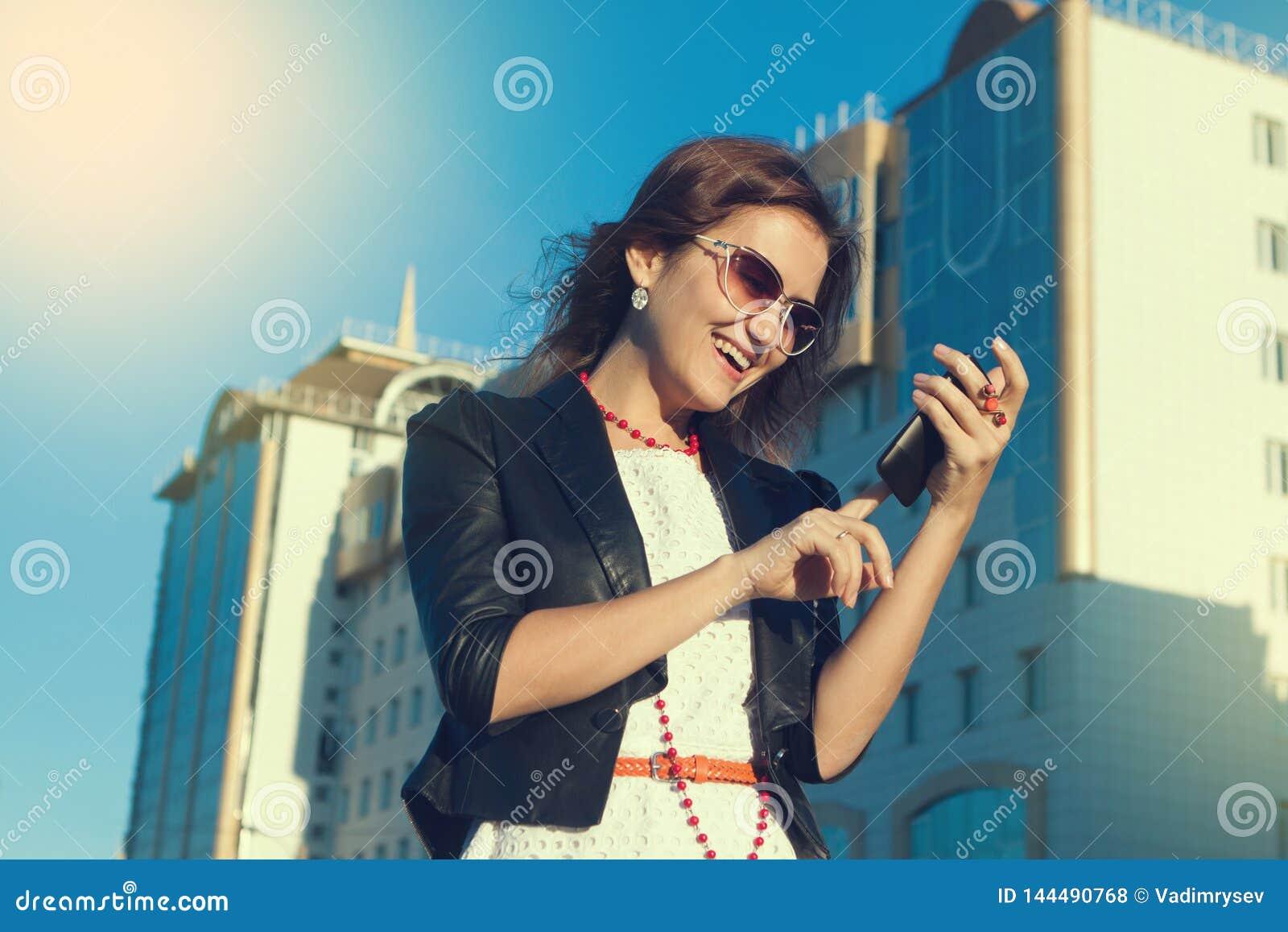 Atrakcyjny bizneswoman używa telefon komórkowego w mieście w sanny dniu