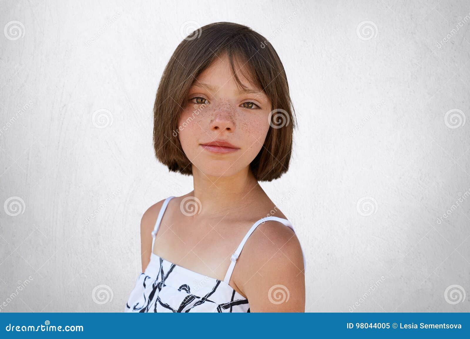 Atrakcyjny brunetka dzieciak z piegami i krótkim włosy pozuje przeciw białej betonowej ścianie ubierał w biel sukni Małe dziecko