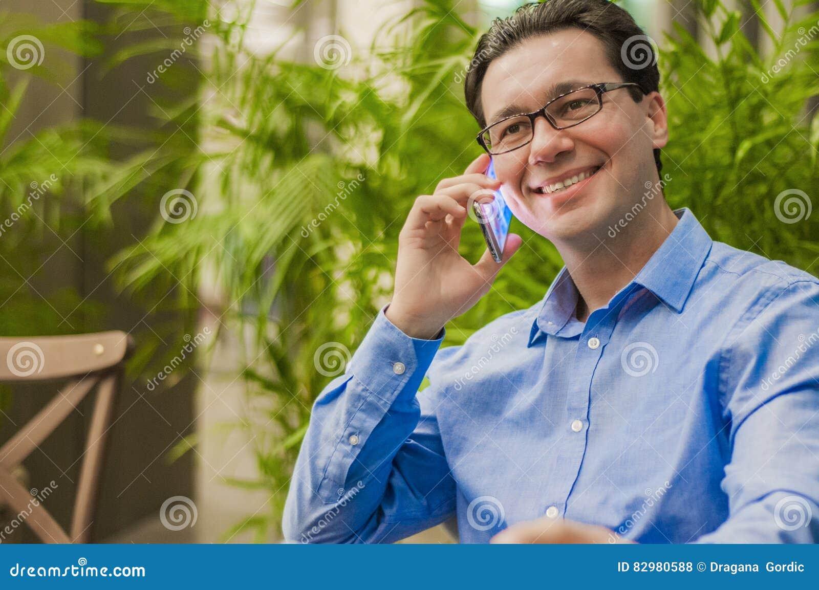 Atrakcyjny i przystojny biznesmen używa telefon komórkowego, azjatykci biznesmen ma telefon rozmowę