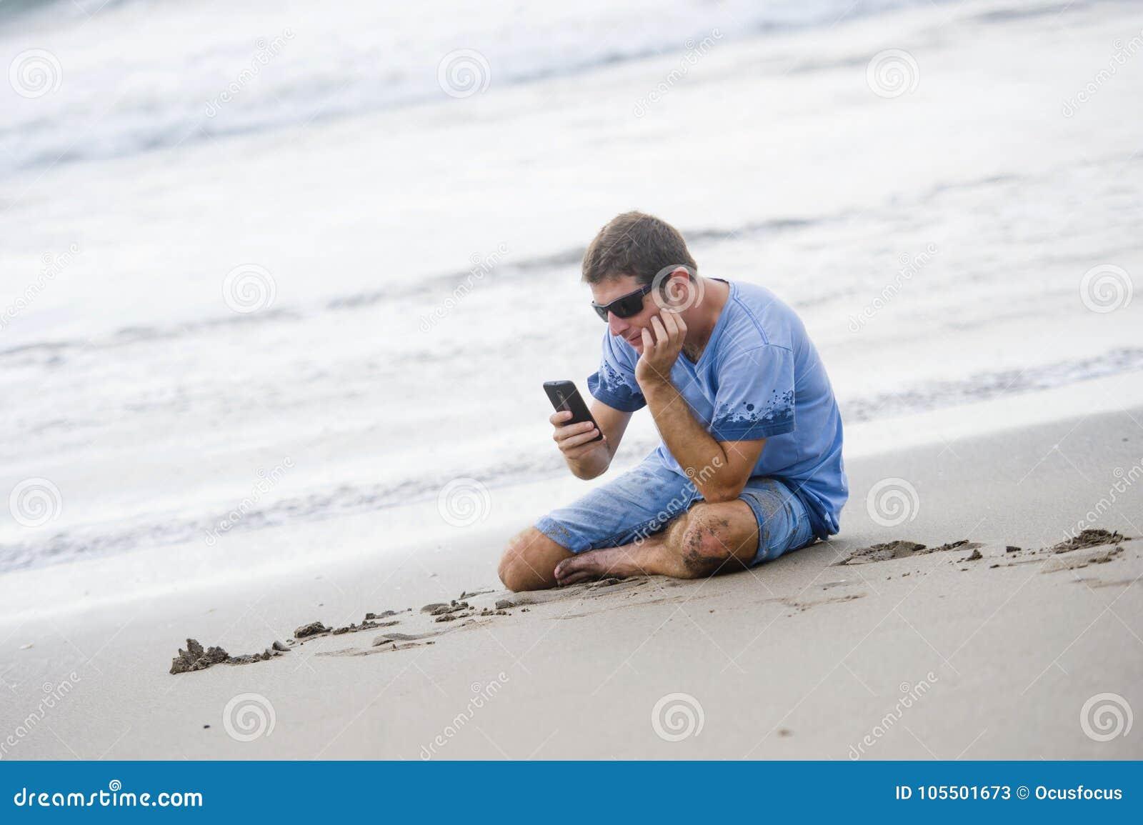 Atrakcyjny i przystojny mężczyzna śmia się przed morzem texting na mobilnym pho na jego 30s obsiadaniu na piasku relaksował na pl
