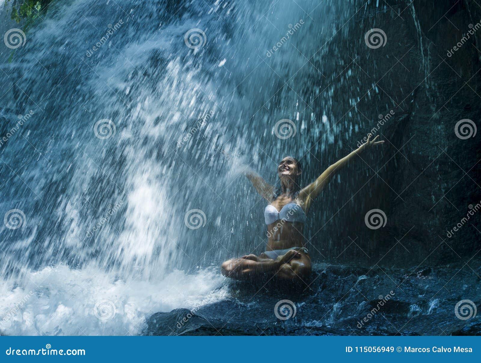 Atrakcyjny kobiety obsiadanie przy skałą w joga pozie dla duchowego relaksu spokoju, medytaci przy oszałamiająco piękną siklawą i