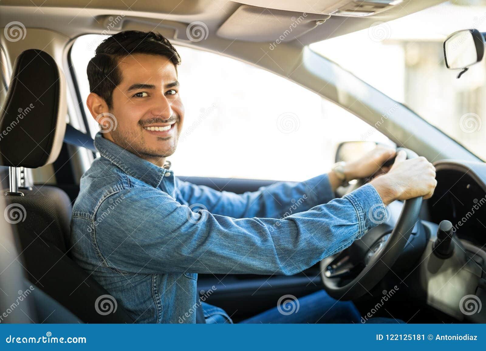 Atrakcyjny mężczyzna jedzie samochód