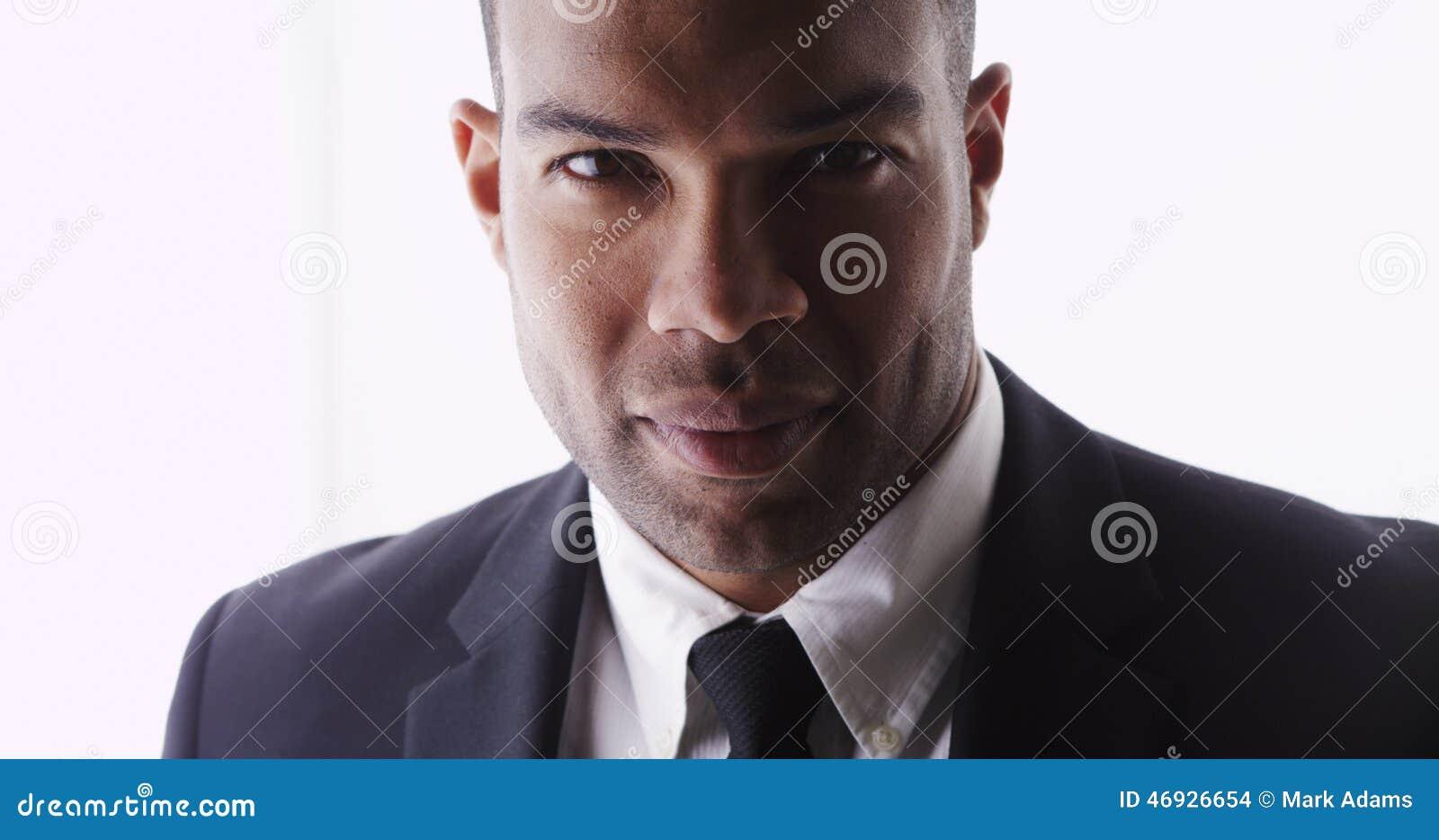 Atrakcyjny mężczyzna patrzeje kamerę jest ubranym kostium