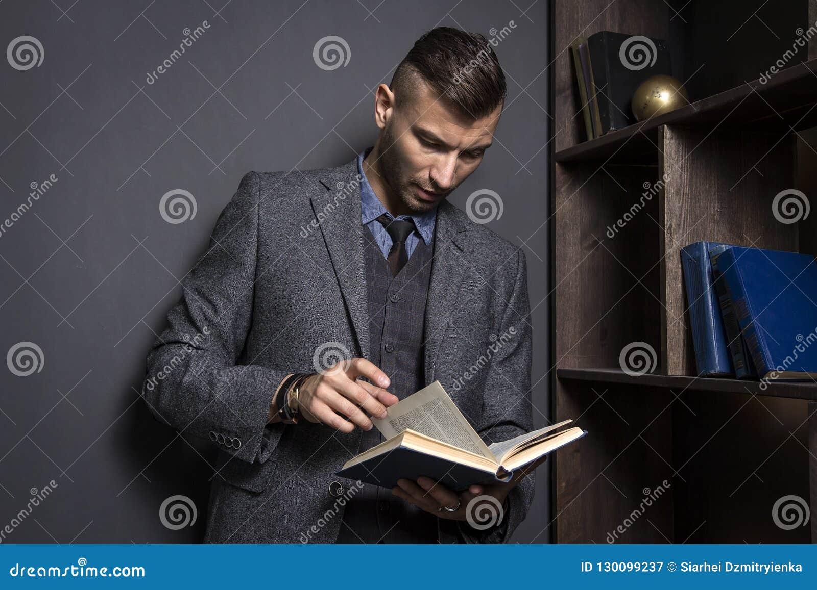 Atrakcyjny mężczyzna w garniturze czyta książkę Prawnik trzyma książkę telefoniczną w jego biurze Uczyć się mężczyzny z książką