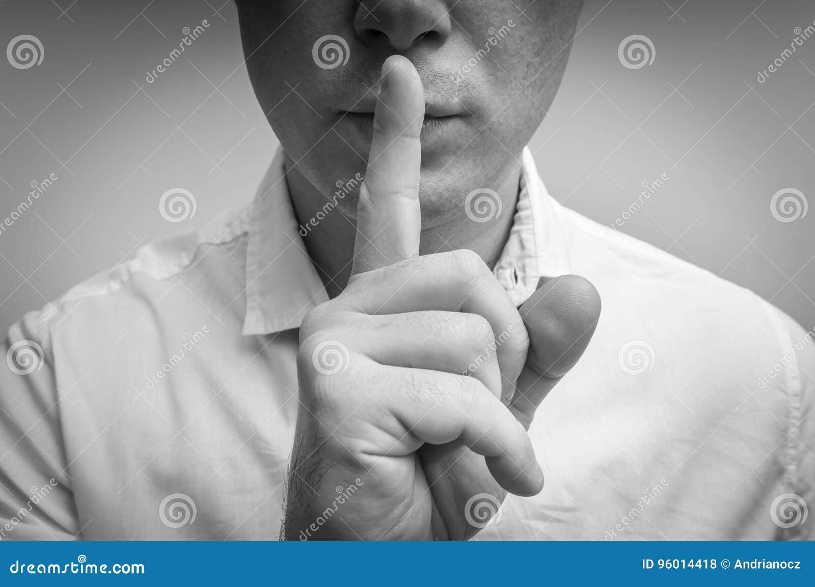 Atrakcyjny mężczyzna z palcem na wargach robi cisza gestowi