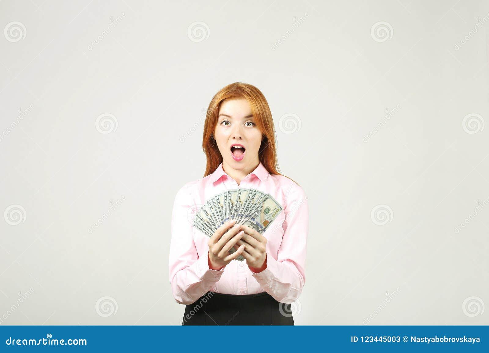 Atrakcyjny młody bizneswoman pozuje z wiązką USD spienięża wewnątrz ręki pokazuje pozytywne emocje i szczęśliwego wyraz twarzy