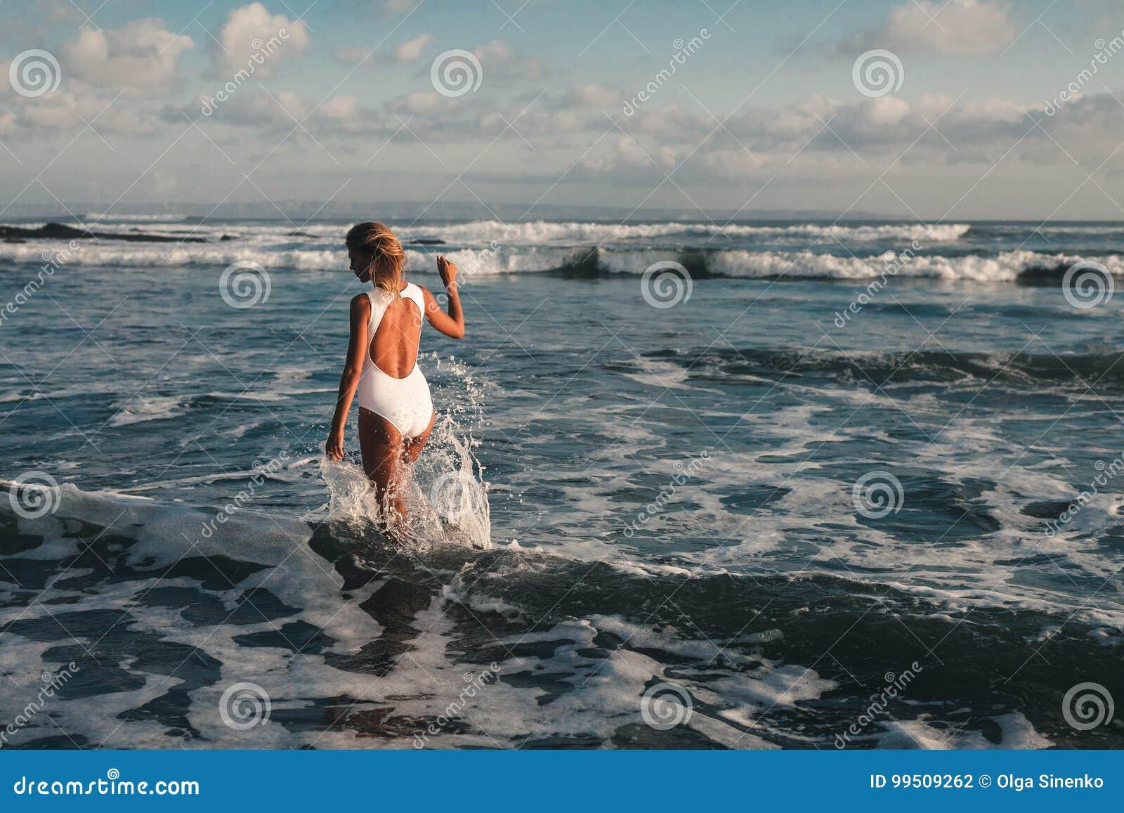 Atrakcyjny młody blondynki kobiety odprowadzenie przy plażą